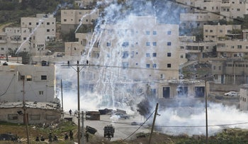 Israeli troops fire tear gas towards Palestinians gathering near the scene of a s suspected stabbing attack, at the West Bank Al-Fawwar refugee camp, south of Hebron, November 25, 2015.