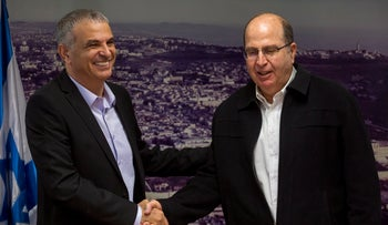 Finance Minister Moshe Kahlon and Defense Minister Moshe Ya'alon shaking hands, November 18, 2015.