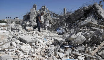 A Palestinian man walks atop the rubble of a house demolished by Israel in the village of Qalandiyah, next to the separation barrier, July 26, 2016.