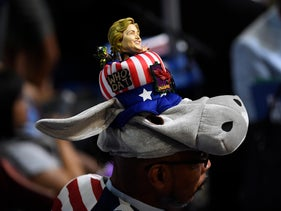 A delegate wears a hat with a bobbled head in the likeness of Hillary Clinton, presumptive 2016 Democratic presidential nominee, during the Democratic National Convention (DNC) in Philadelphia, Pennsylvania, U.S., on Monday, July 25, 2016.