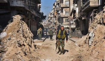 Syrian pro-government forces walk through a barricade in old Aleppo's Jdeideh neighborhood, Syria, December 9, 2016.