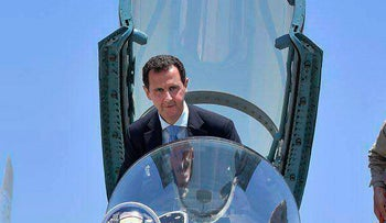 FILE -- in this June 27, 2017 file photo and released on the official Facebook page of the Syrian Presidency, Syrian President Bashar Assad climbing into the cockpit of a Russian SU-35 fighter jet as he inspects the Russian Hmeimim air base in the province of Latakia, Syria. (Syrian Presidency via AP, File)