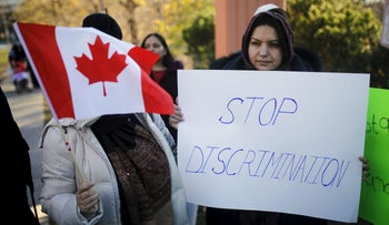 People holds signs during a solidarity march in Toronto, November 20, 2015.