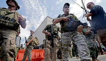 """Armed nationalist militias evacuate comrades who were pepper sprayed after the """"Unite the Right"""" rally was declared an unlawful gathering,in Charlottesville, Virginia  August 12, 2017."""