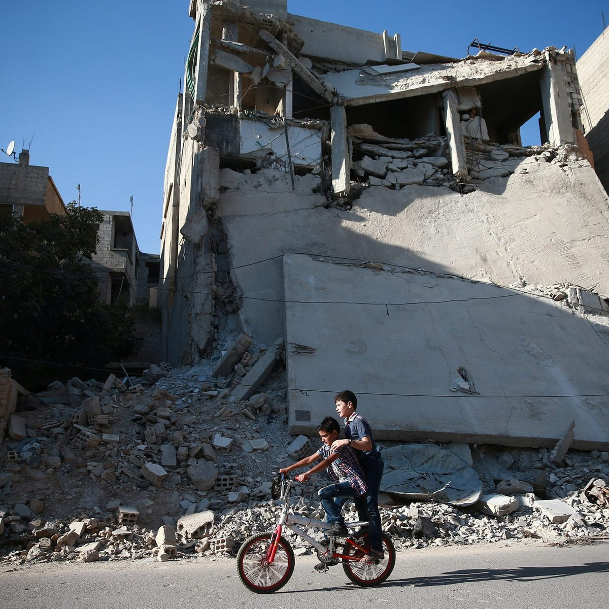 Boys ride a bicycle near rubble of damaged buildings in Douma, near Damascus, Syria August 14, 2017.