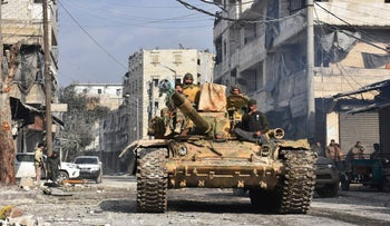 Syrian pro-government forces patrol Aleppo's eastern al-Salihin neighborhood after troops retook the area from rebel fighters, Syria, December 12, 2016.