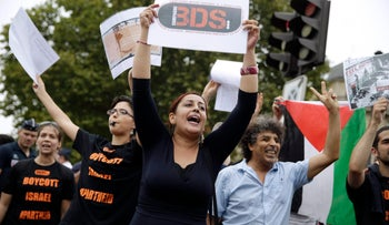"""A Pro-Palestinian protester holds a placard reading """"BDS"""" during a gathering on the sidelines of a beach event celebrating Tel Aviv, Paris, August 13, 2015."""