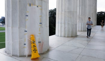 Tourists walks past a papered-over column where a vandal scrawled obscene graffiti in spray paint on the Lincoln Memorial in Washington, U.S. August 15, 2017. REUTERS/Jonathan Ernst