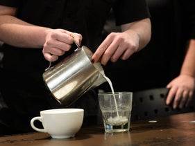 File photo: A barista pours milk into a glass to prepare a cup of coffee.