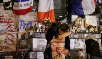 Two people hug in front of the place de la Republique monument in Paris after a priest was killed in Normandy on July 26, 2016.