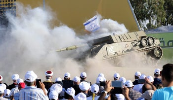 Hezbollah supporters watch a reenactment of an attack on an Israeli tank to mark the anniversary of the end of the Second Lebanon War, in southern Lebanon, August 13, 2017.