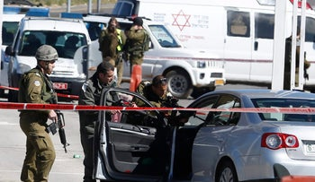 Israeli security forces inspect the body of a Palestinian identified as Amjad Sukkari, inside a car, at the checkpoint between the city of Ramallah and Jewish settlement of Beit El in the West Bank. Sukkari opened fire at a West Bank checkpoint and wounded three people, the Israeli military said.