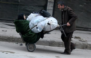 A man pushes a cart carrying an elderly woman and belongings as they flee deeper into the remaining rebel-held areas of Aleppo, Syria December 12, 2016.