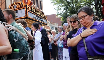 Clergy observe a moment of silence during the memorial service for Heather Heyer outside the Paramount Theater in Charlottesville, Virginia, August 16, 2017.