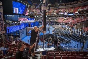Workers attach a Kansas state sign to a mic pole inside the Wells Fargo Center ahead of the Democratic National Convention (DNC) in Philadelphia, U.S., on Sunday, July 24, 2016.