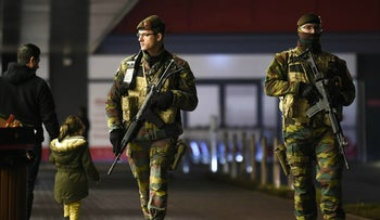 Two armed Belgian soldiers walking on patrol past a father and daughter, at a shopping center near Vervier, Belgium, on November 25, 2015.