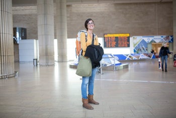 Hadas Asscher, a 30-year-old woman wearing jeans, a yellow sweater and brown boots, stands at the airport.