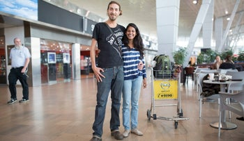 Uriel Kramer, 31, and Jayanti Tamby, 33, stand at the airport embracing each other.