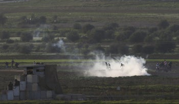 Palestinian protesters run from tear gas fired by Israeli soldiers during clashes, as seen from the Israeli side of the border fence, November 27, 2015.