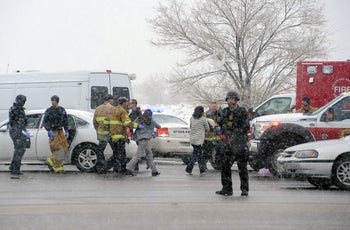 A woman is escorted by emergency personnel after reports of a shooting near the Planned Parenthood clinic Friday, Nov, 27, 2015, in Colorado Springs, Colo.