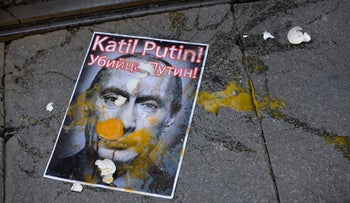 A picture depicting Russian President Vladimir Putin is splattered with eggs during a protest against Russian military operations in Syria in Istanbul, Turkey, Oct. 3, 2015.