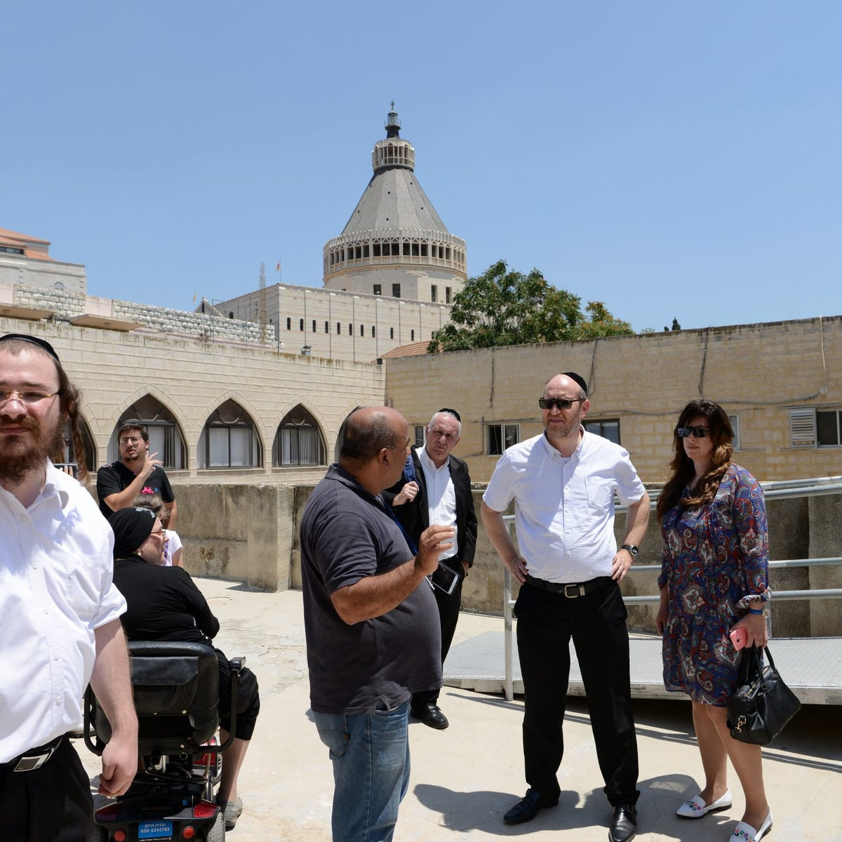 Tour guide Ibrahim (center) escorting the group of Haredi Jews around Nazareth. The Church of the Annunciation is in the background.