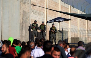Israeli Border Police officers stand guard as Palestinians wait to cross through the Qalandiyah checkpoint, June 2016.