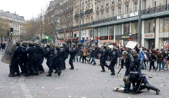 French CRS riot police take cover behind shields during clashes with demonstrators near the Place de la Republique after the cancellation of a planned climate march, Paris, November 29, 2015.