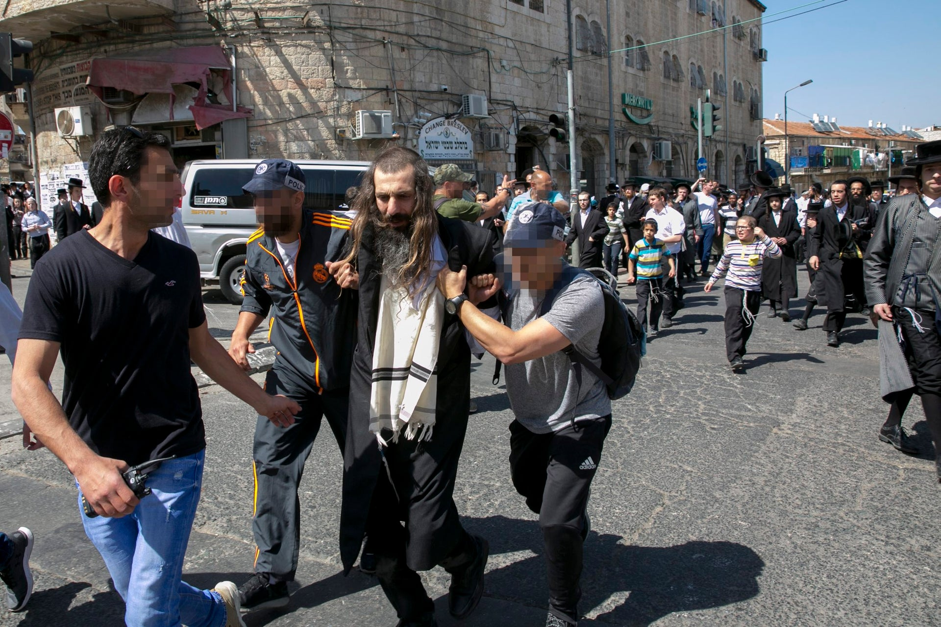 A member of the ultra-Orthodox community being led away following a police operation in Mea She'arim, April 2017.
