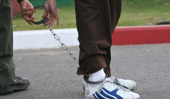 A close-up of the legs of a prisoner, wearing leg restraints, which are being opened by a police officer as the inmate is lead to court.