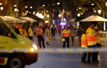 Emergency workers stand on a blocked street in Barcelona, Spain, Thursday, Aug. 17, 2017.