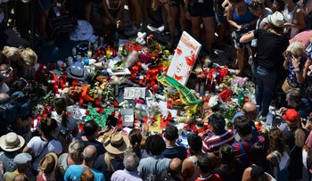People gather at the spot where a van plowed into a crowd on the Rambla Boulevard in Barcelona, on August 18, 2017.