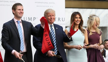 Donald Trump, together with his family, from left, Eric, Melania and Tiffany, waves part of a ribbon after cutting the ribbon during the grand opening of Trump International Hotel in Washington.