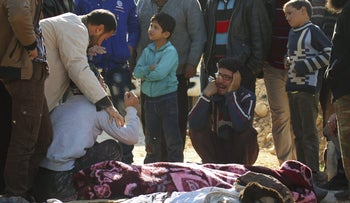 People mourn over bodies of civilians, who died during what activists said were airstrikes carried out by the Russian air force on a busy market place in the town of Ariha, Syria November 29, 2015.