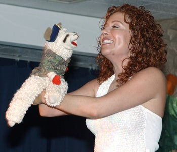 Mallory Lewis, wearing a white shirt and smiling at her sheep puppet, who seems to be wearing camouflage, appearing at the Bob Hope Primary School at Kadena Air Base in Japan.