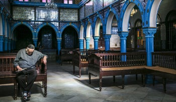 A Jewish man rests in La Ghriba, the oldest synagogue in Africa, on the Island of Djerba, southern Tunisia, October 28, 2015.