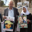 Suha and Hussein Abu Khdeir, center, parents of Mohammed Abu Khdeir, hold posters with his portrait after the reading of the verdict in his killing, at the Jerusalem District Court, Monday, Nov. 30, 2015.