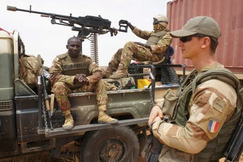 French and Malian soldiers wait for an armored car to be dug out of sand in Inat, Mali, May 2016.
