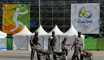 Workers carrying tools in wheelbarrows next to the Tennis Stadium in Rio de Janeiro, Brazil August 1, 2016