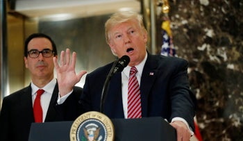 President Donald Trump, accompanied by Treasury Secretary Steven Mnuchin, speaks to the media in the lobby of Trump Tower in New York on Tuesday August 15, 2017.