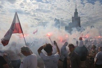 People stand on Warsaw's main intersection holding burning flares to commemorate the 72nd anniversary of the 1944 Warsaw Uprising, Warsaw, Poland, August 1, 2016.
