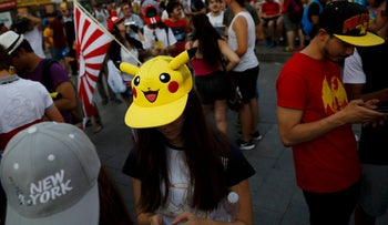 Fans play Pokemon Go during a gathering in central Madrid, Spain, July 28, 2016.