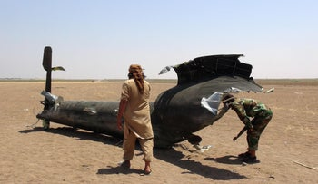This photo reportedly shows Syrian rebels inspecting the wreckage of a Russian military transport helicopter after it was shot down in northern Syria on August 1, 2016.