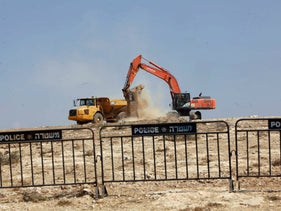 A bulldozer demolishes a building in a Bedouin village in Israel.