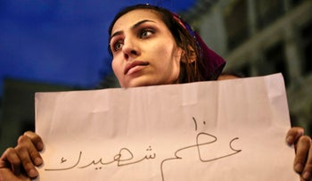 """A woman holds a paper with Arabic that reads, """"hold your martyr high,"""" during a vigil for victims of a Sunday bombing at a Coptic cathedral, in downtown Cairo, Egypt, December 14, 2016."""