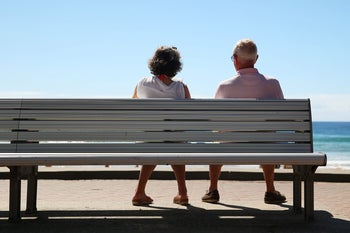 An older man and woman, seen from behind, sit beside each other on a bench on a boardwalk facing the sea in Sydney.