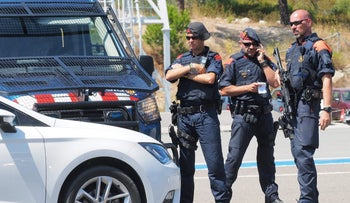 Spanish police officers check vehicles as they cross the Spanish-French border between La Jonquera northern Spain, and Le Perthus, southern France, August 20, 2017.