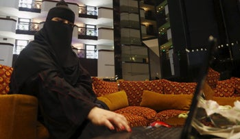 Saudi woman Fawzia al-Harbi, a candidate for local municipal council elections, uses her laptop at a shopping mall in Riyadh November 29, 2015.
