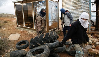 Israeli youths move tyres as they construct a temporary barrier in the Jewish settler outpost of Amona in the West Bank December 15, 2016.