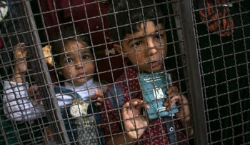A Palestinian child holding a passport as he waits at the Rafah border crossing with Egypt, in the southern Gaza Strip, May 11, 2016.